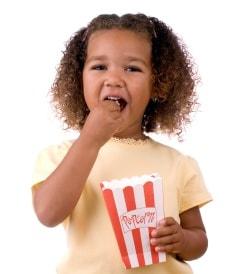 little girl eating popcorn