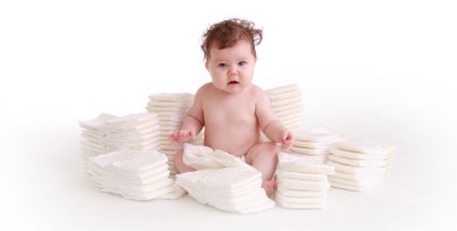 baby surrounded by diaper stacks