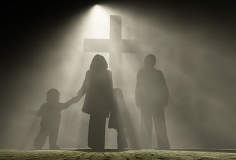 Family standing at the foot of a cross