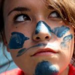 Teenage girl with paint on her face during a mission project.