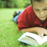 boy reading a book in the summertime
