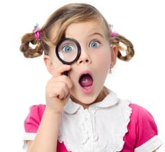 Girl looking through a magnifying glass