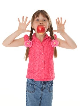 Little girl with hands raised & apple in mouth.