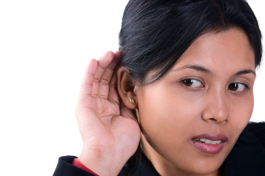 A woman trying to listen the sound around her