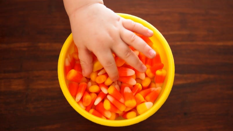 Toddler hand selects candy corn from a yellow Halloween bowl